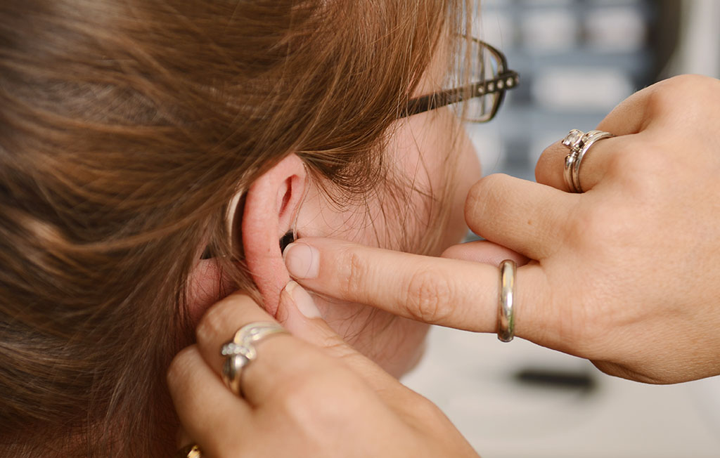 A patient is fitted with a new hearing aid at Speech Therapy & Audiology, Columbus Regional Health