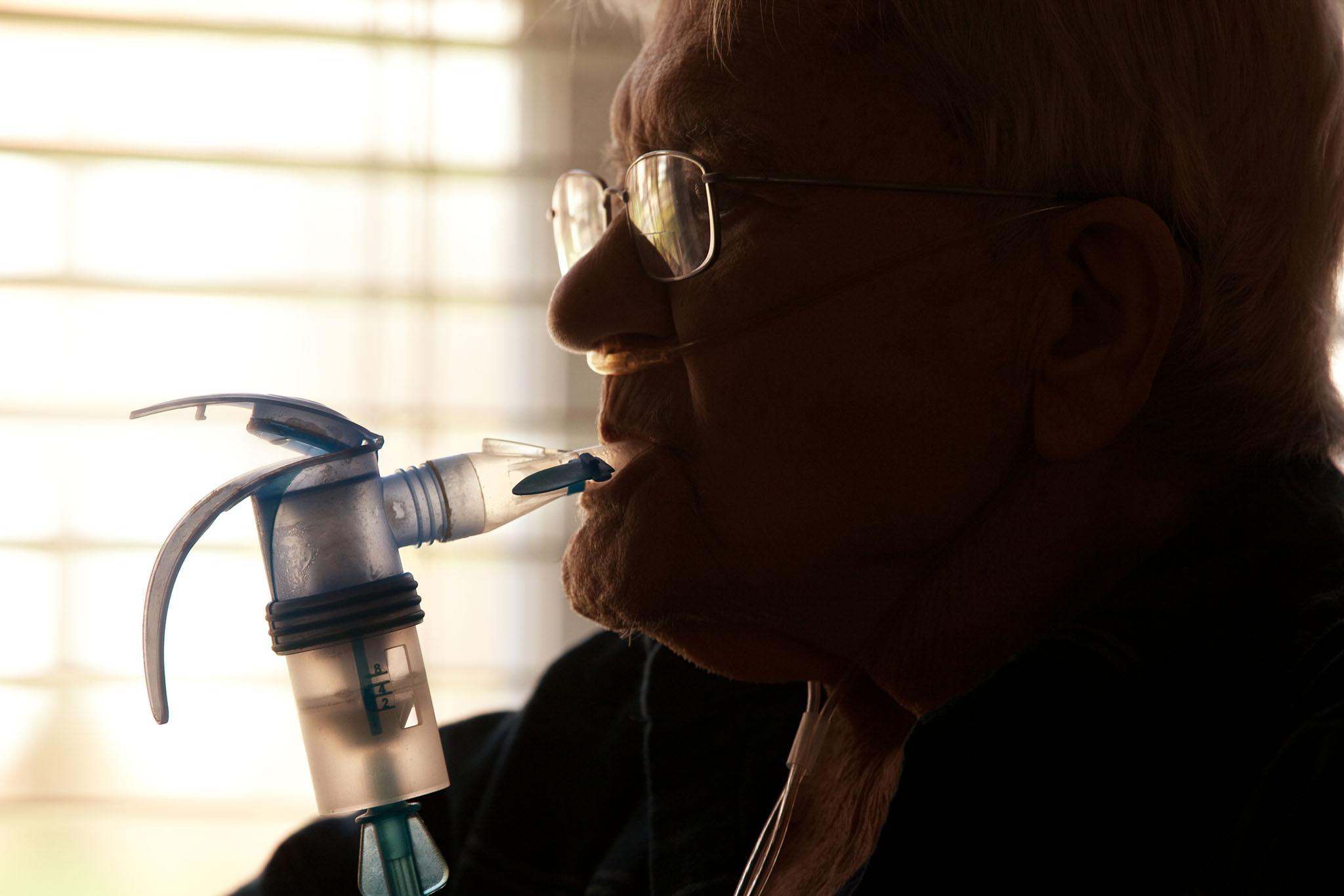 Elderly man using COPD inhaler