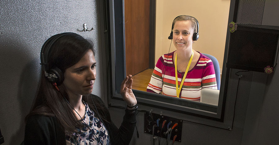Laura Burger performs a hearing test in soundproof booth