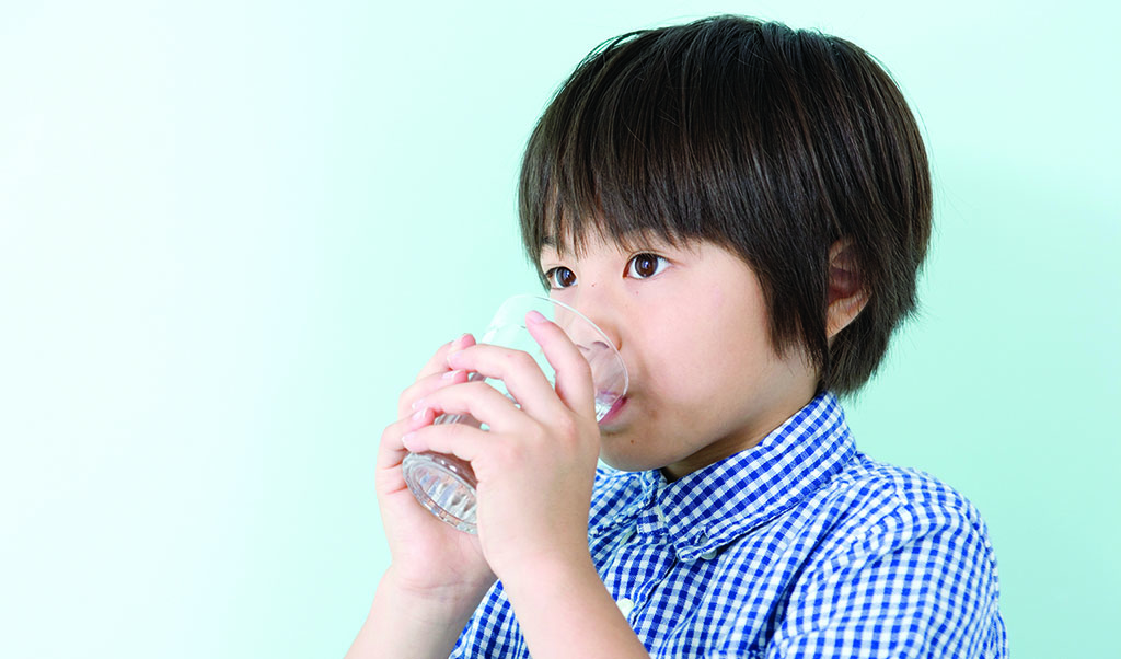 young child drinking glass of water