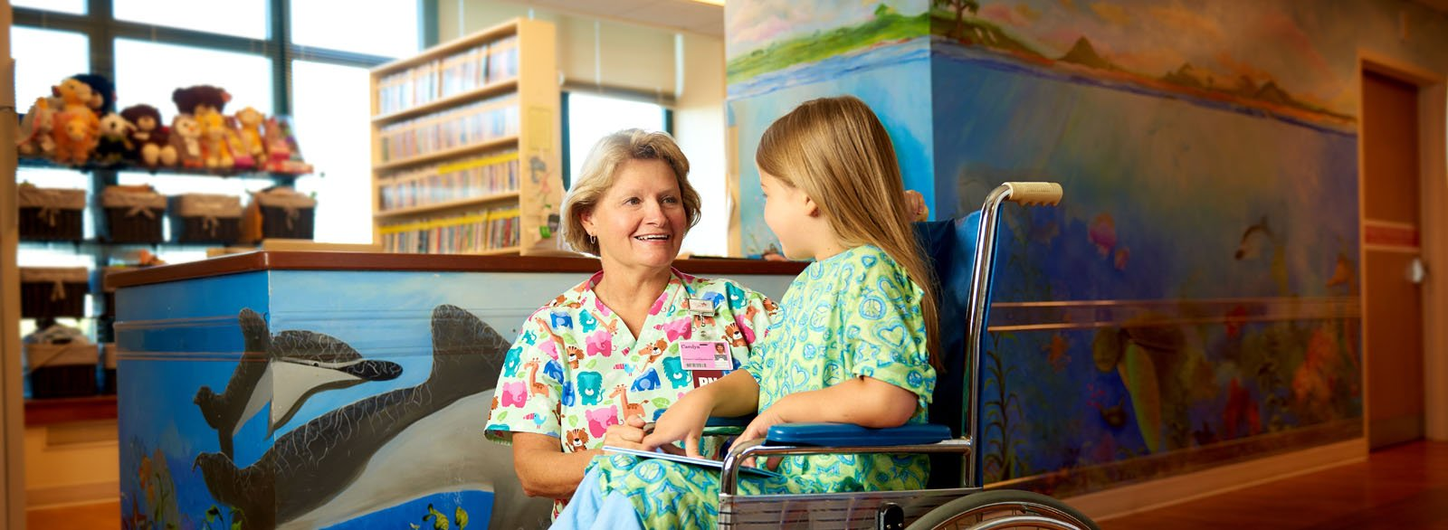 Nurse visiting with young girl in the pediatrics unit at Columbus Regional Hospital.
