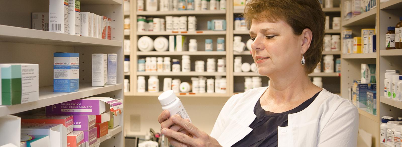 VIMCare pharmacist reading label on bottle of medicine