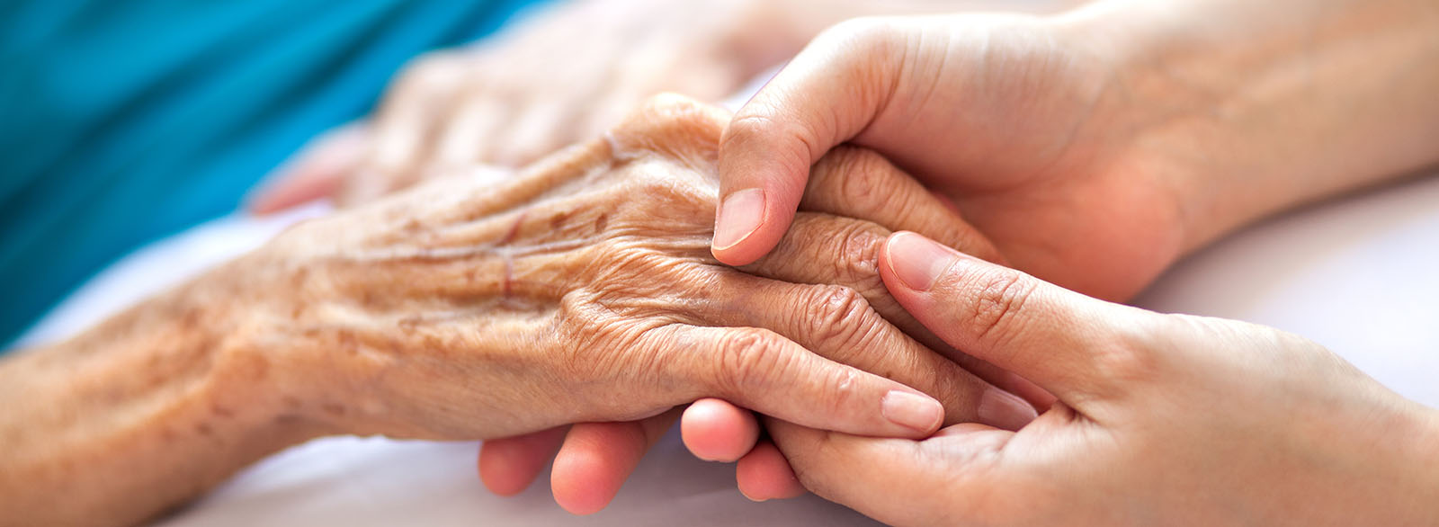 Elderly hand clasped with younger hands