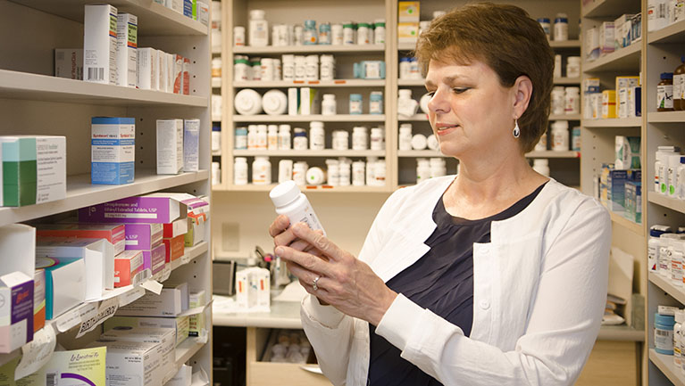 VIMCare pharmacist reading label on bottle of medicine