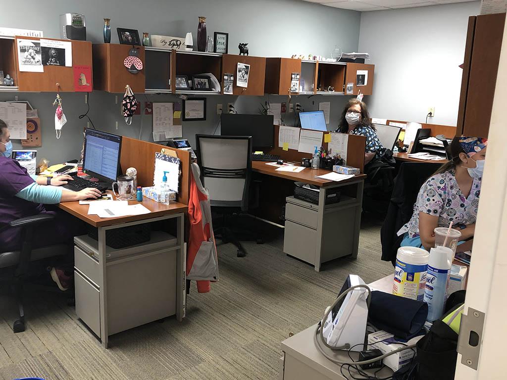 COVID-19 Registry staff wearing masks, working in office.