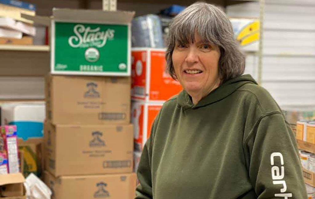 Kathy Sage with shelves of food in the background.