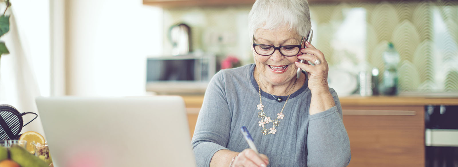 Older woman on cell phone in front of laptop.
