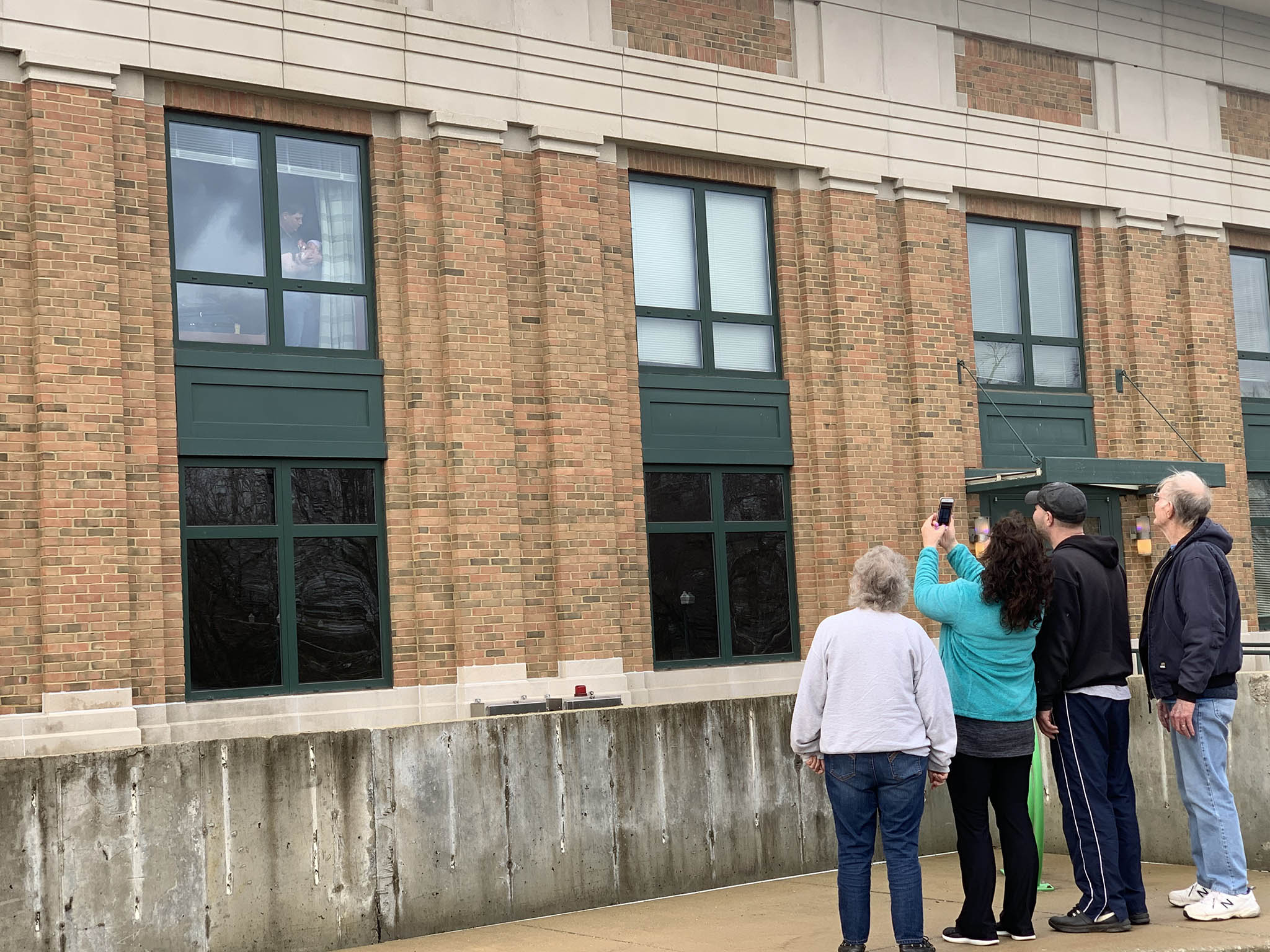 A family takes pictures of a father holding a newborn baby in the window at Columbus Regional Hospital.