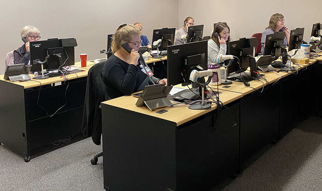 Nurses talking on telephones in a COVID-19 Triage Resource Call Center.