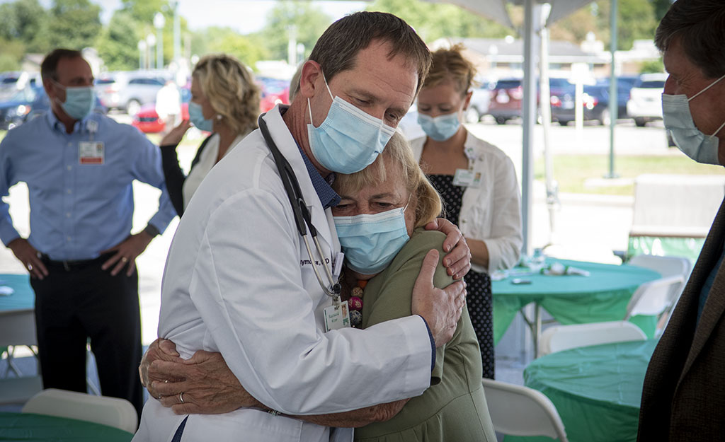Dr. Lee Kiser hugs CRH board member Sherry Stark during a ceremony in his honor.