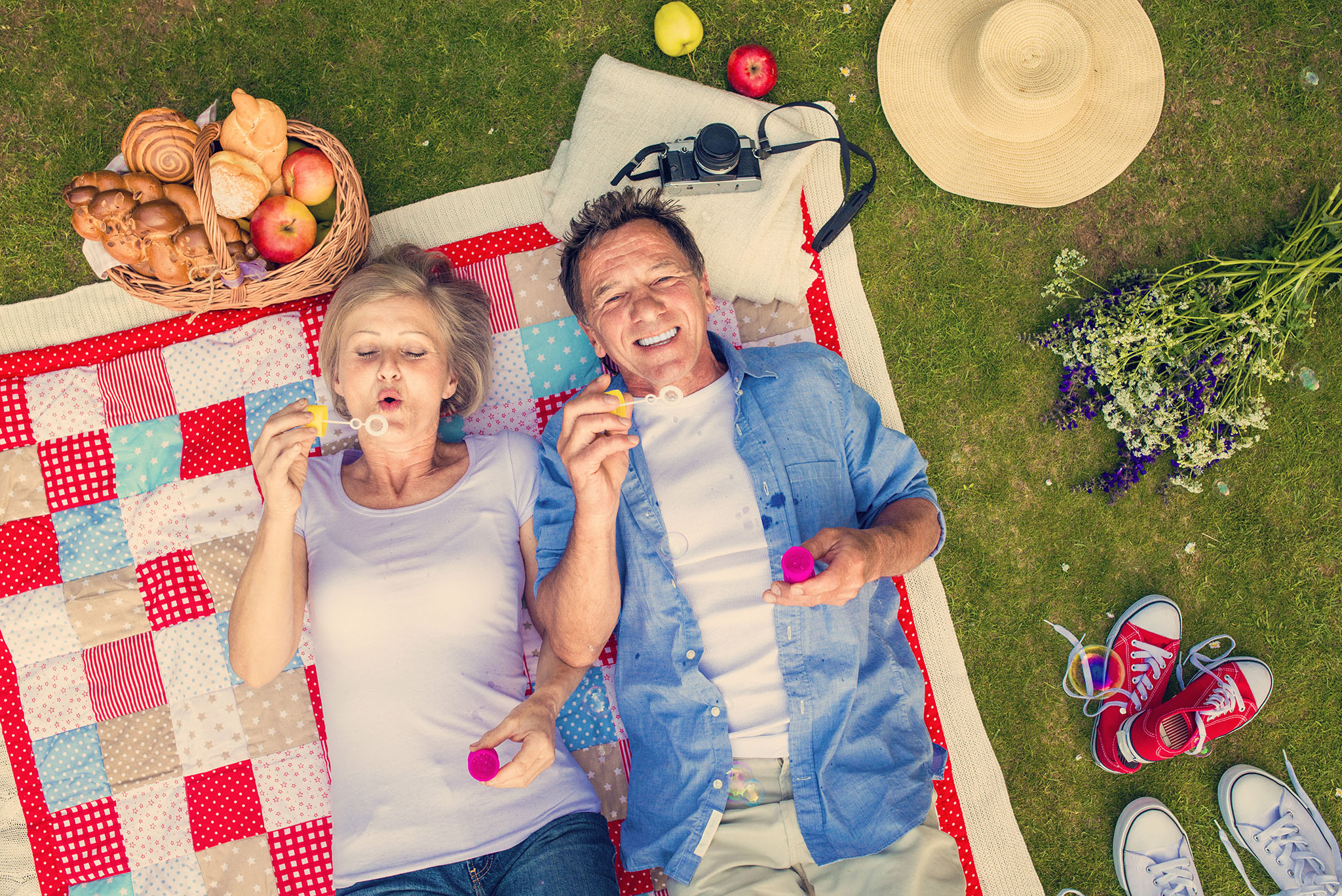 Middle-aged couple on picnic blanket blowing bubbles together