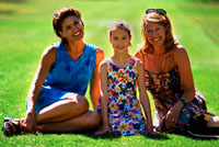 Picture of two women and a teenage girl sitting on a picnic blanket
