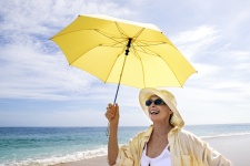 Photo of woman at the beach demonstrating sun protection strategies