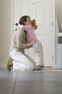 Woman kneeling on floor hugging a toddler