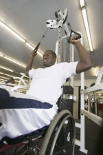 Photo of young man in wheelchair lifting weights