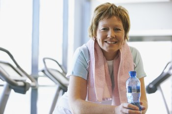 Photo of a middle aged woman at the gym. She is looking at the camera and holding a water bottle. Exercise machines are lined up behind her.