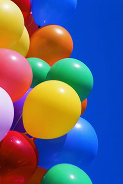 A cluster of colorful balloons agains a blue sky.