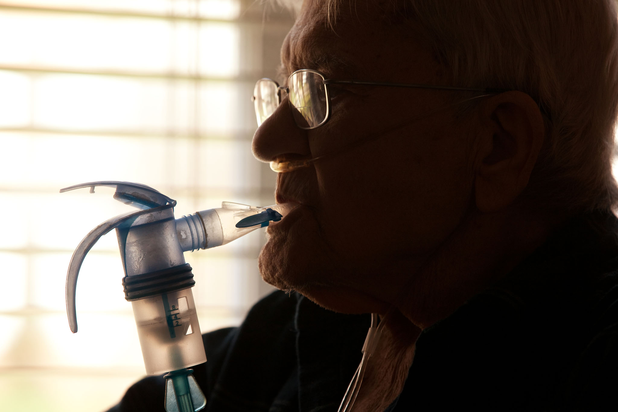 Elderly man using COPD inhaler