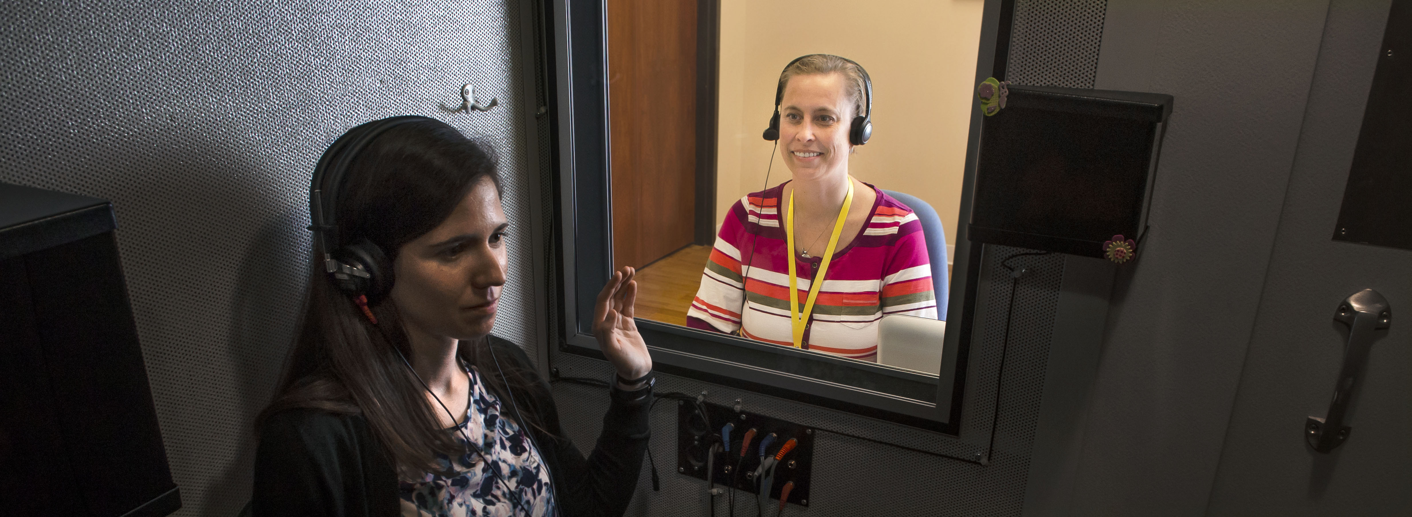 Laura Burger performs a hearing test on a patient in a soundproof booth