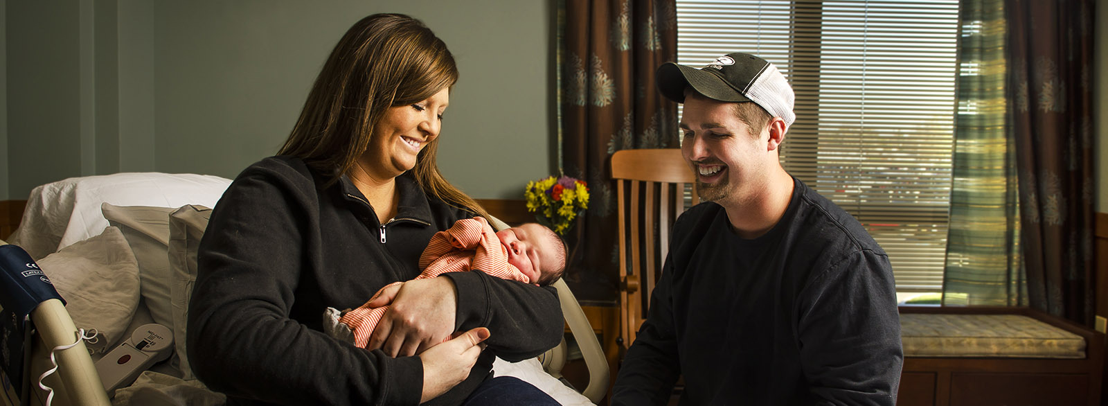 New mother holding her baby with husband nearby in the Birthing Center at Columbus Regional Health.