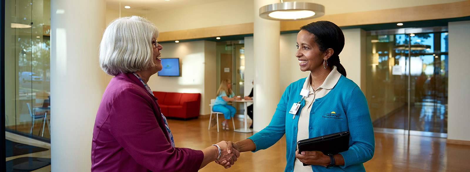 Connection specialist greeting a visitor with a handshake at WellConnect