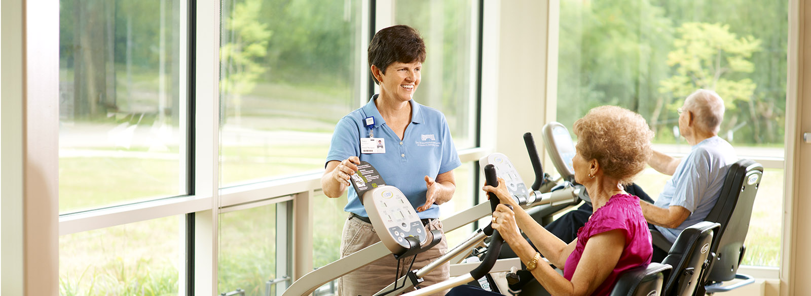Wellness instructor with seniors on equipment at Mill Race Center