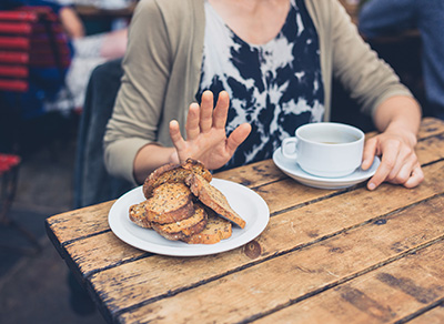 Woman holding up her hand to a plate of toast.