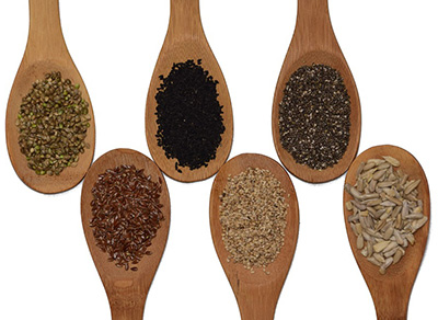Arranged wooden spoons with various seeds in them.