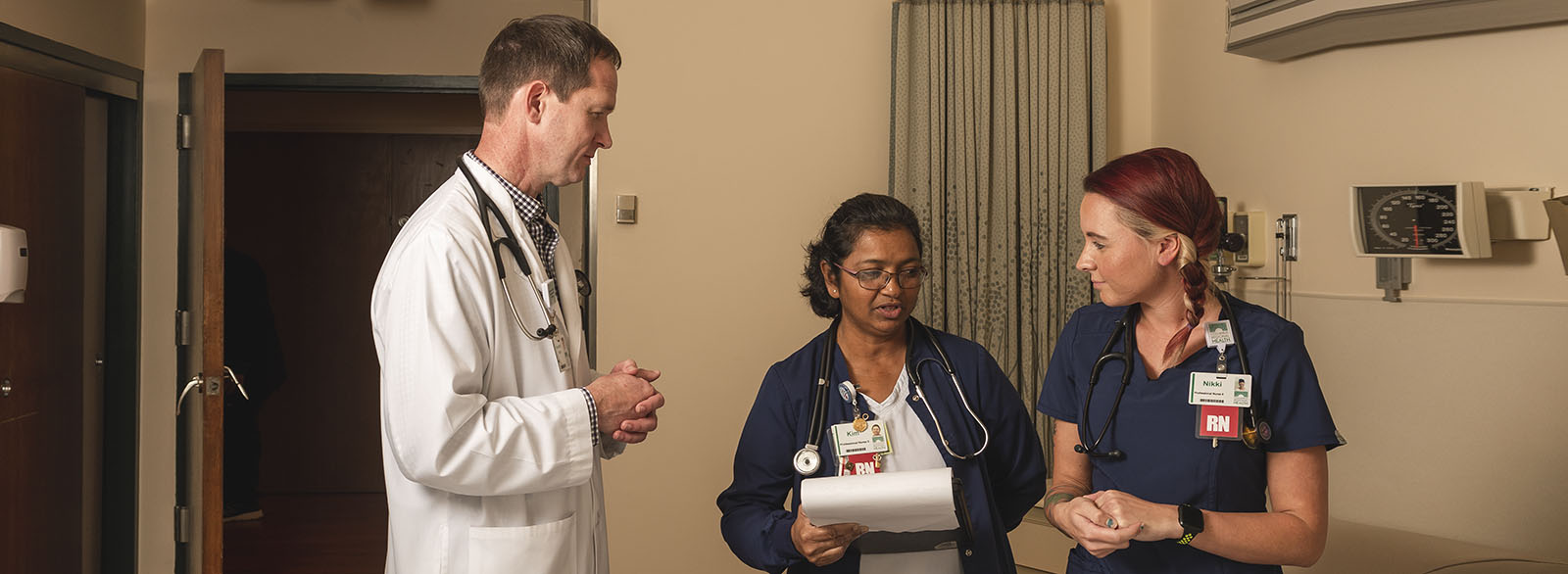 Physician preceptor speaking with nurses in a patient room.